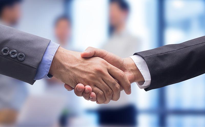 契約を結ぶ握手をしている写真